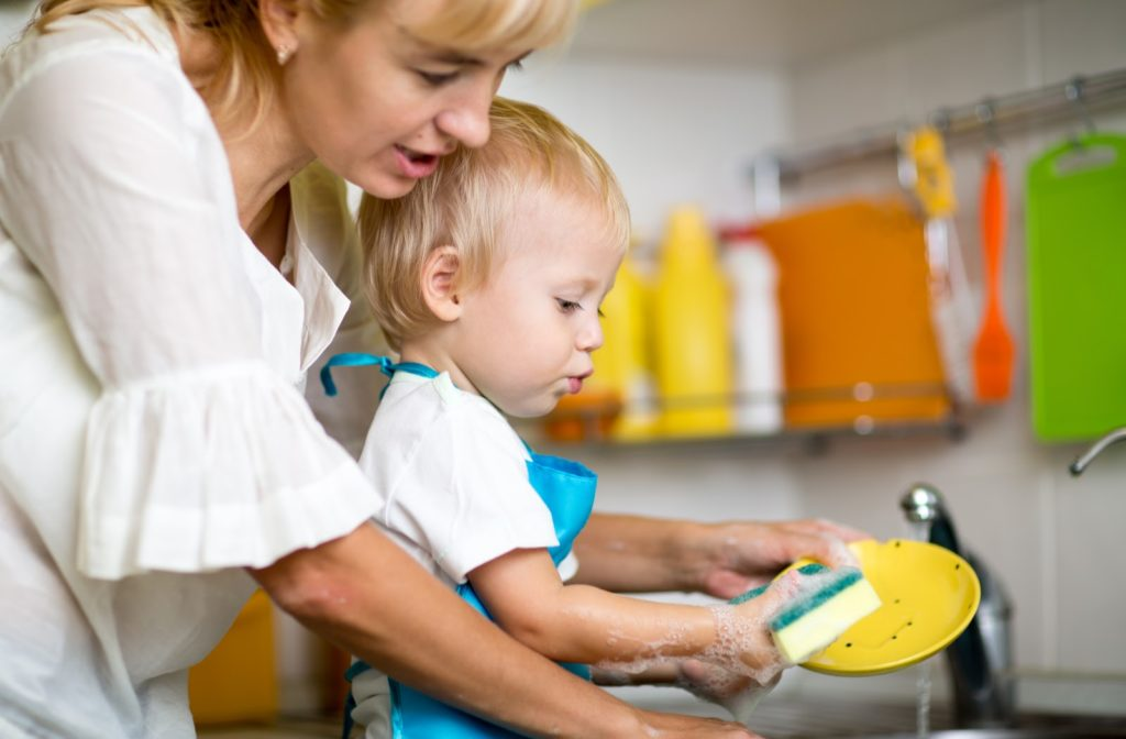 Mother teaching her child how to do the dishes.