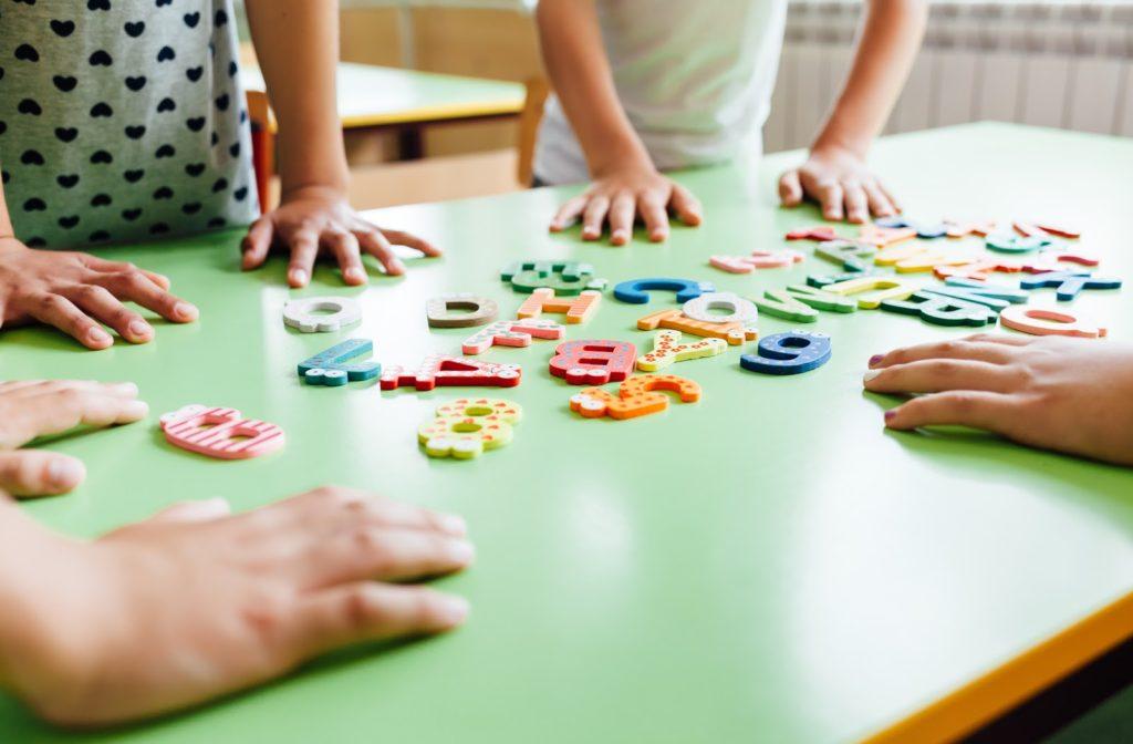 Children using social skills to share alphabet blocks.