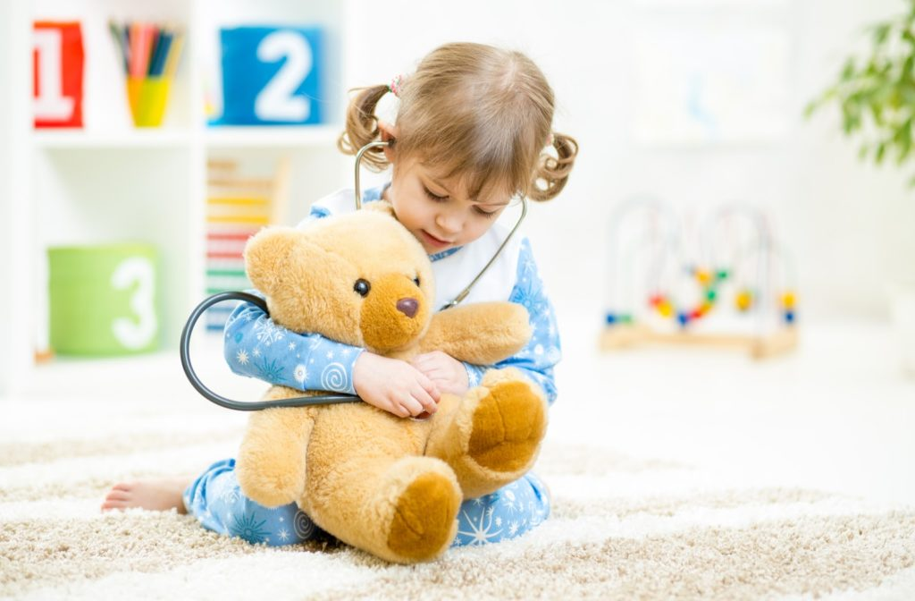 Young girl playing doctor with a teddy bear.