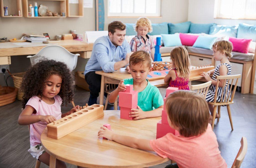 A teacher guiding students in a Montessori classroom