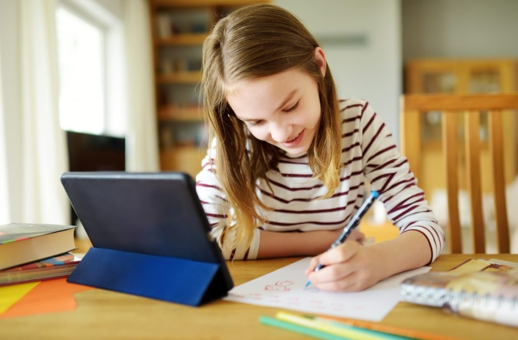An older child working on her homework with the help of a tablet