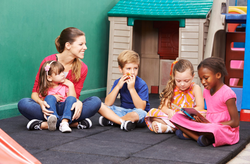 A group of four preschool kids sitting outside reading out loud to each other