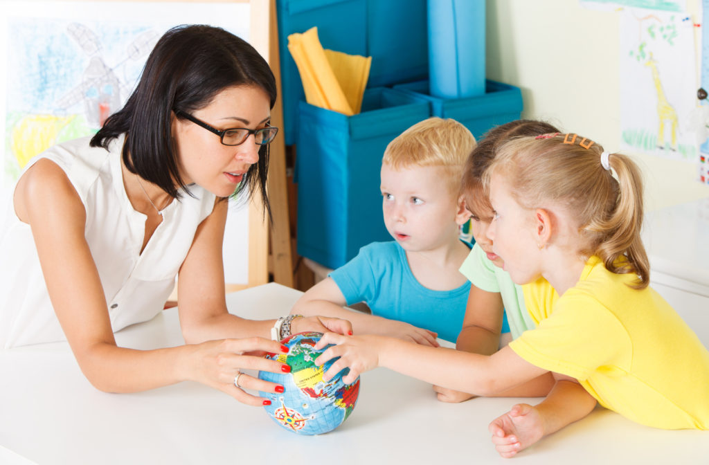 A small group of preschool kids looking at a globe while their teacher teaches them about it