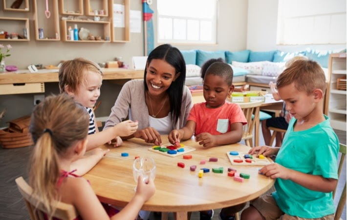 Teacher with four children sitting at a table using wooden shapes in a Montessori school