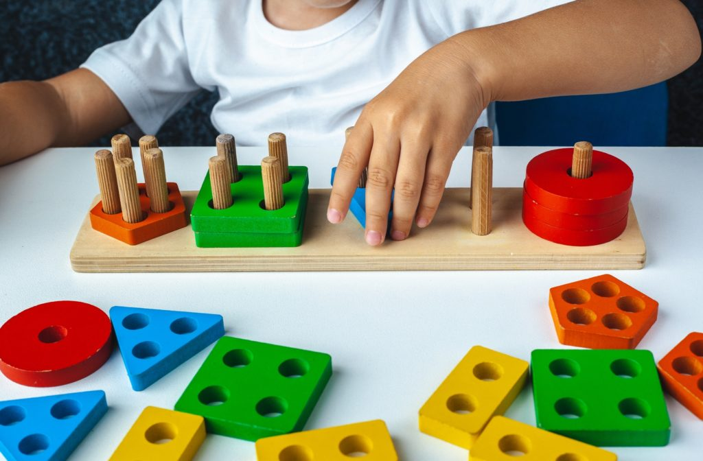 A young child playing with coloured, wooden Montessori games