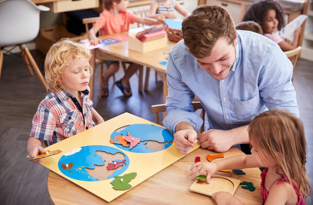 A teacher helping his students sitting at a table with wooden shapes in a Montessori school