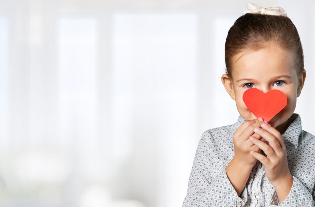 A little girl holding up a heart cut out symbolizing respectfulness and discipline